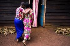 BUKAVU, REPUBLIQUE DEMOCRATIQUE DU CONGO. AVRIL 2016. Zawadi (a gauche avec sa tante), victime de viol prise en charge par la fondation Panzi, retourne dans son village de Kavunu pour voir sa mere. La fondation Panzi prend en charge des femmes victimes de viol et developpe un programme de rehabilitation par le sport.