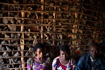 BUKAVU, REPUBLIQUE DEMOCRATIQUE DU CONGO. AVRIL 2016. Zawadi (au milieu entouree de sa tante et de son pere), victime de viol prise en charge par la fondation Panzi, retourne dans son village de Kavunu pour voir sa mere. La fondation Panzi prend en charge des femmes victimes de viol et developpe un programme de rehabilitation par le sport.